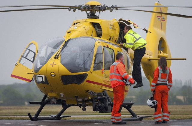 Britain's Prince William checks his helicopter as he begins his new job as a co-pilot with the East Anglian Air Ambulance (EAAA) at Cambridge Airport, Britain July 13, 2015. (Photo by Stefan Rousseau/Reuters)