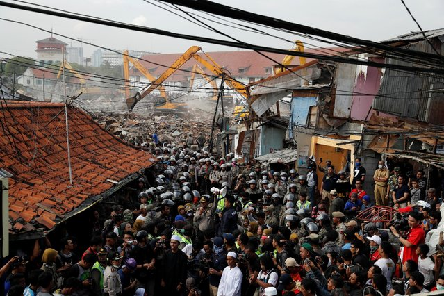 Policemen shout to warn residents before an eviction as machinery demolishes illegal houses at Luar Batang fisheries village in Jakarta, Indonesia, April 11, 2016. (Photo by Reuters/Beawiharta)