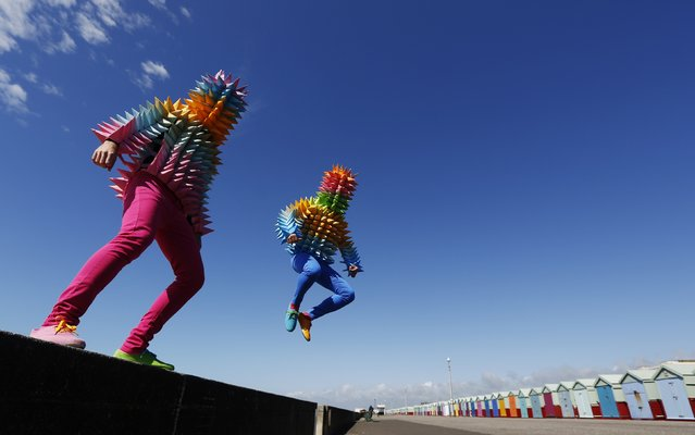 """Venezuelan artist Cristobal Ochoa (L) and his performance partner Jean-Paul Fowler promote the Artist Open Houses part of the Brighton Festival with street art performance """"Los conos de madre"""" (""""Mother's cones""""), on the seafront in Brighton May 6, 2014. (Photo by Luke MacGregor/Reuters)"""