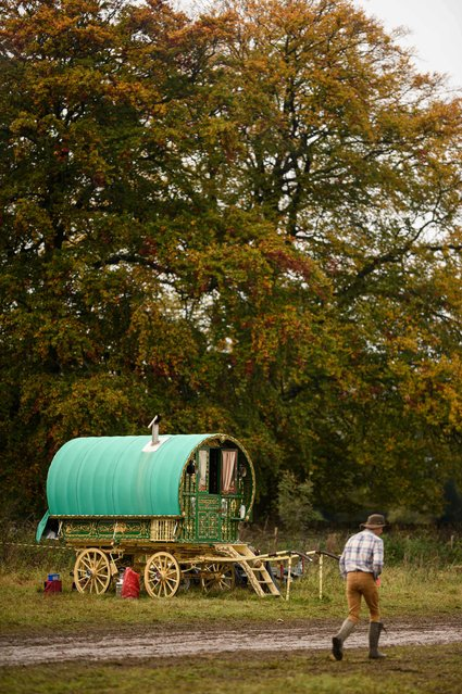 A young man walks past a traditional Gypsy caravan at the biannual Stow Horse Fair in the town of Stow-on-the-Wold, England on October 24, 2019. (Photo by Oli Scarff/AFP Photo)