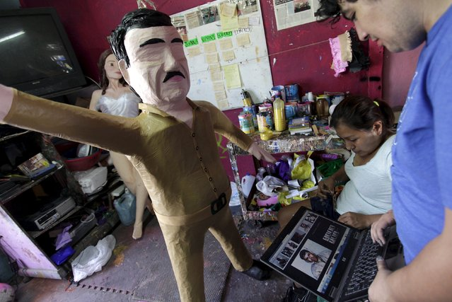 "Workers refer to images on a  laptop in front a pinata depicting drug lord Joaquin ""El Chapo"" Guzman at a workshop in Reynosa, July 21, 2015. (Photo by Daniel Becerril/Reuters)"