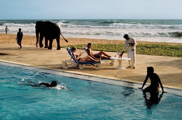 Tourists lounge poolside as an elephant passes, Bentota, Sri Lanka, 1995. (Photo by Steve McCurry/The Guardian)