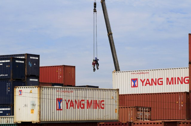 Workers hang on ropes as they assist heavy machinery in arranging cargo containers at a shipping yard in Cavite city, south of Manila July 23, 2015. The Philippines will likely miss its export growth target of 8-10 percent this year after shipments contracted in the first five months of 2015, its trade secretary said on Wednesday. (Photo by Romeo Ranoco/Reuters)
