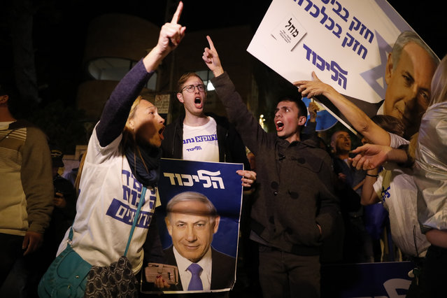 Supporters of Israeli Prime Minister Benjamin Netanyahu gather outside his residence in Jerusalem, Thursday, November 21, 2019. Israel's attorney general charged Netanyahu with fraud, breach of trust and accepting bribes in three different scandals. It is the first time a sitting Israeli prime minister has been charged with a crime. (Photo by Ariel Schalit/AP Photo)