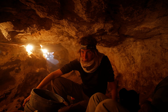 A volunteer with the Israeli Antique Authority works inside the Cave of the Skulls, an excavation site in the Judean Desert near the Dead Sea, Israel June 1, 2016. (Photo by Ronen Zvulun/Reuters)