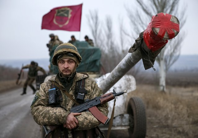 A member of the Ukrainian armed forces stands guard as a convoy of the Ukrainian armed forces including armoured personnel carriers, military vehicles and cannons prepare to move as they pull back from the Debaltseve region, in Paraskoviyvka, eastern Ukraine, February 26, 2015. Ukrainian troops towed artillery away from the front line in the east on Thursday, a move that amounted to recognising that a ceasefire meant to take effect on Feb. 15 was holding at last. (Photo by Gleb Garanich/Reuters)