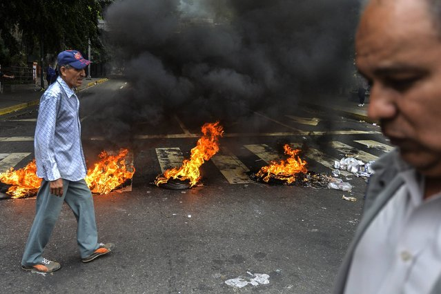"""People walk past a roadblock during clashes between opposition demonstrators and riot police in a protest against the government of President Nicolas Maduro in Caracas, on June 5, 2017. Prominent opposition leader jailed in Venezuela, Leopoldo Lopez, urged more street protests against the """"tyranny"""" of President Nicolas Maduro, in a video message made in his cell and released on Sunday. Lopez, 46, however stressed several times that he backed only """"peaceful"""" demonstrations. (Photo by Luis Robayo/AFP Photo)"""