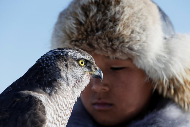 A young hunter holds his tamed hawk during a traditional hunting contest outside the village of Kaynar in Almaty region, Kazakhstan on December 8, 2019. (Photo by Pavel Mikheyev/Reuters)
