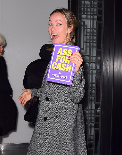 """Olivia Wilde has spent many years behind the scenes at SNL, while hubby Jason Sudeikis was a regular on the weekly comedy show, and she might've earned some perks in the process. The actress was seen heading into the SNL After Party on December 22, 2019, holding onto a One of a Kind Prop, which was used by Eddie Murphy in a Sketch. She made off with a book, titled """"a*s for Cash"""" by Velvet Jones , a character played by Eddie in """"Black Jeopardy"""". Olivia showed it off as she arrived to the party with her Husband Jason. (Photo by DIGGZY/Splash News and Pictures)"""