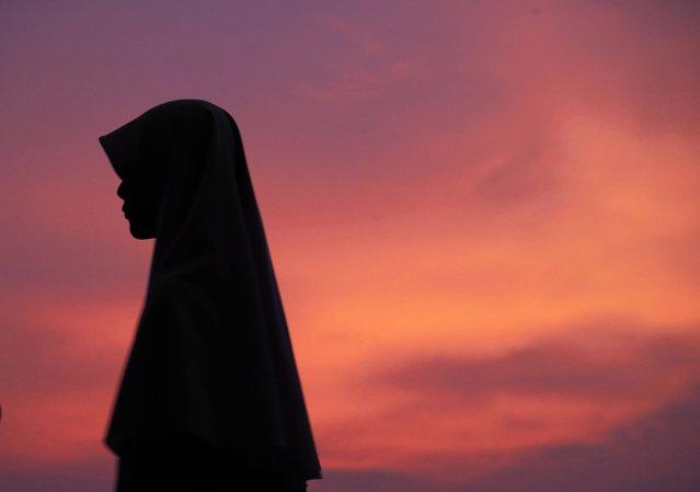 A Malaysian Muslim woman waits for the announcement to mark the start of the fasting month of Ramadan in Putrajaya, outside Kuala Lumpur, Malaysia, on June 27, 2014. (Photo by Shamshahrin Shamsudin/European Pressphoto Agency)