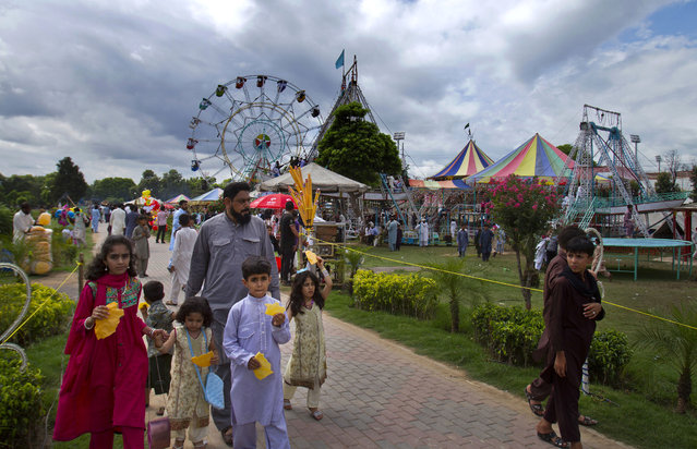 Pakistani families visit a park to celebrate the Eid al-Fitr holidays in Rawalpindi, Pakistan, Saturday, July 18, 2015. Eid al-Fitr marks the end of the holy month of Ramadan, during which Muslims all over the world fast from sunrise to sunset. (Photo by Anjum Naveed/AP Photo)