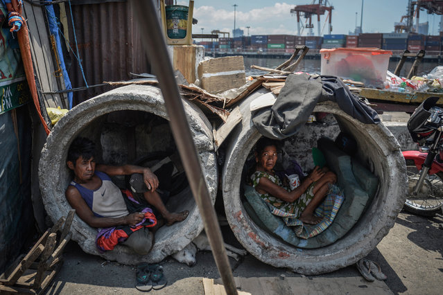 A homeless man and woman rest inside concrete drainage pipes in a slum area on April 26, 2017 in Manila, Philippines. (Photo by Ezra Acayan/Barcroft Images)