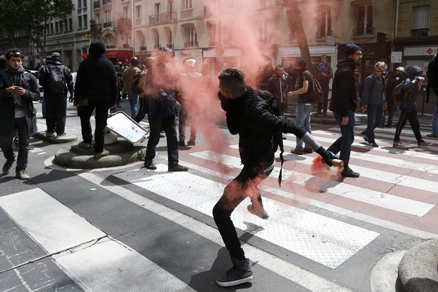 epaselect epa05363899 A protester throws back a tear gas canister during clashes with riot police during a national demonstration and strike against the Labor Law reform in Paris, France, 14 June 2016. Labor unions demonstrated during a national strike across France to protest against about employment law reforms in the so-called El Khomri bill. (Photo by Yoan Valat/EPA)
