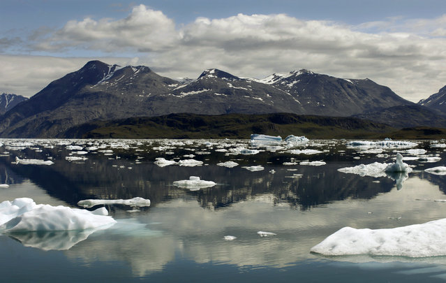 Icebergs are reflected in the waters of Eriks Fjord near the town of Narsarsuaq in southern Greenland. (Photo by Bob Strong/Reuters)