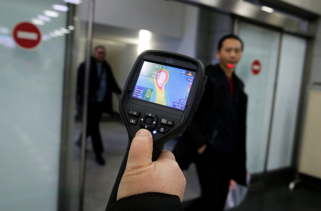 Kazakh sanitary-epidemiological service worker uses a thermal scanner to detect travellers from China who may have symptoms possibly connected with the previously unknown coronavirus, at Almaty International Airport, Kazakhstan on January 21, 2020. (Photo by Pavel Mikheyev/Reuters)