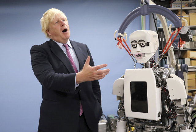 Britain's Foreign Secretary Boris Johnson gestures as he looks at a humanoid robot at Research Institute for Science and Engineering at Waseda University's campus in Tokyo Thursday, July 20, 2017. Johnson visited the robotics center at the university, which collaborates with the University of Birmingham, according to Britain's Foreign and Commonwealth Office. (Photo by Eugene Hoshiko/AP Photo)