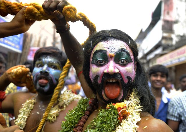 "An Indian Hindu male devotee dressed as a woman dances during the festival of ""Bonalu"", a ritual offering to the goddess Kali, at the Sri Ujjaini Mahakali Temple in Secunderabad on July 13, 2014. The goddess Kali is honoured mostly by women during the Bonalu festival through offerings of food and dances. (Photo by Noah Seelam/AFP Photo)"