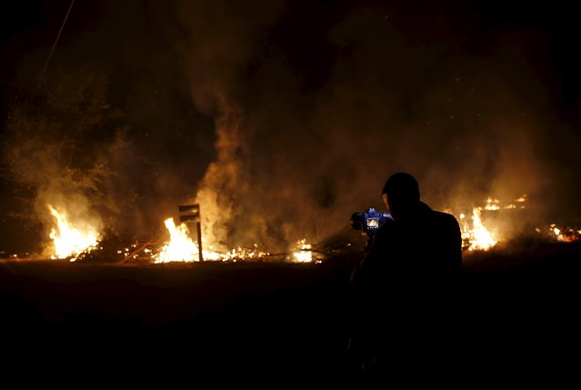 A photographer takes photographs of flames at the Jerusalem Fire in Lake County, California August 12, 2015. (Photo by Robert Galbraith/Reuters)