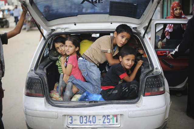 Palestinian children sit in a car boot as they flee their family homes following heavy Israeli shelling during an Israeli ground offensive east of Khan Younis, in the southern Gaza Strip July 23, 2014. Israeli forces pounded multiple sites across the Gaza Strip on Wednesday, including the enclave's sole power plant, and said it was meeting stiff resistance from Hamas Islamists, as diplomats sought to end the bloodshed. (Photo by Ibraheem Abu Mustafa/Reuters)