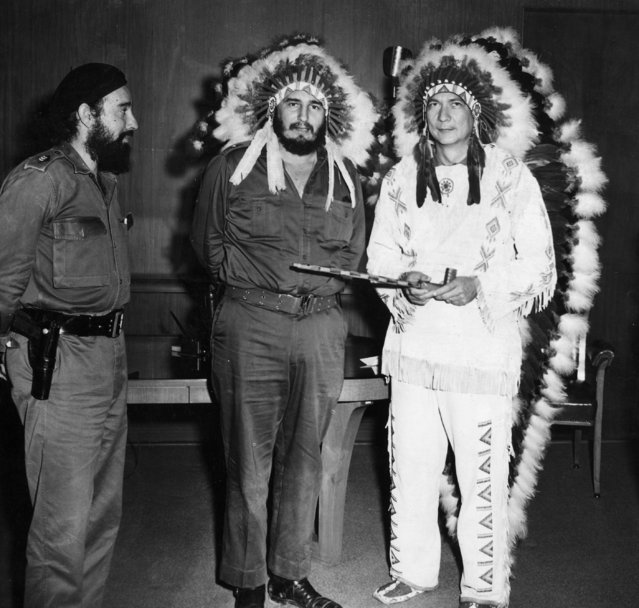 Cuban Premier Fidel Castro, center, and Oklahoma Creek Indian missionary, W.A. Reiford, wear war bonnets, July 17, 1959, when Reiford came to Havana to open an orphanage.  Reiford holds a peace pipe. At left, Capt. Antonio Nunez Jimenez looks on. (Photo by AP Photo)