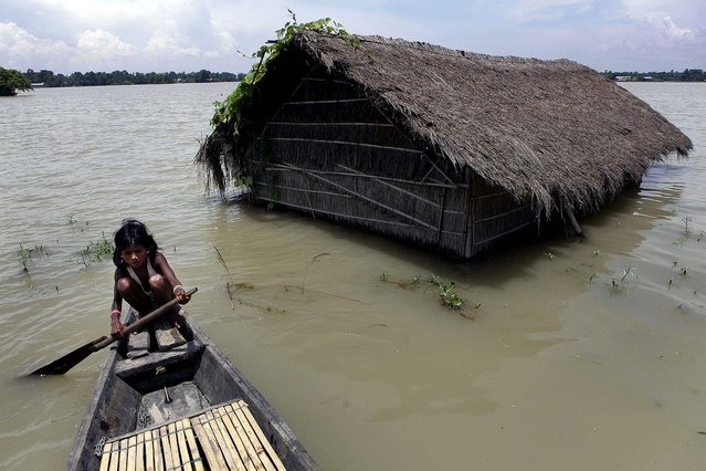A girl rows a boat near her submerged house in Burhaburhi village, India on July 20, 2012. Days of continuous rainfall has raised the water level of the Brahmaputra River and its tributaries and flooded the area. (Anupam Nath/Associated Press)