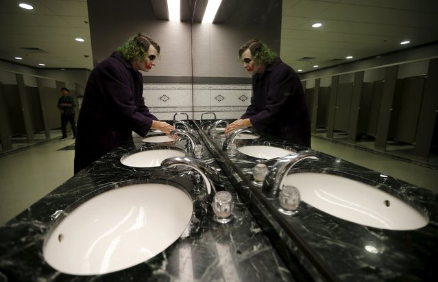 """Erik Slone dressed up as """"The Joker"""" washes his hands in the restroom while waiting for the start of the costume contest at Wizard World Comic Con in Chicago, Illinois, United States, August 22, 2015. (Photo by Jim Young/Reuters)"""