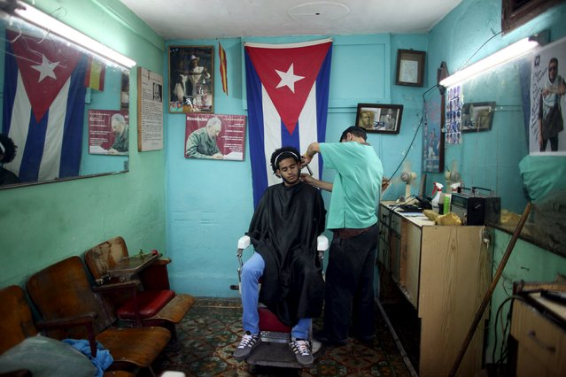 Jose Cisneros, 24, who recently graduated from university where he studied Economics and is looking for a job, has his hair cut by Enrique David, 26, in Havana, February 4, 2015. (Photo by Alexandre Meneghini/Reuters)