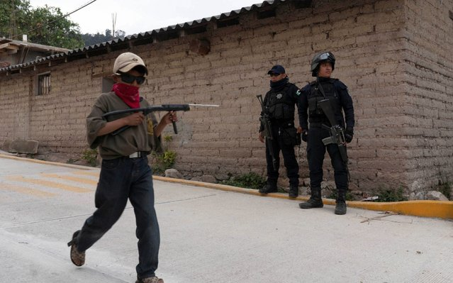 Reinel Toribio, 9, walks past state police officers holding a toy gun, as he demonstrates newly learnt skills from military-style weapons training, to a Reuters journalist, in Ayahualtempa, Mexico, February 3, 2020. (Photo by Alexandre Meneghini/Reuters)