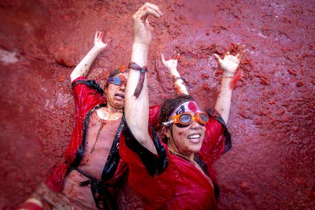 """Revellers slide around in tomato pulp during the annual """"Tomatina"""" festivities in the village of Bunol, near Valencia on August 26, 2015. Some 22,000 revellers hurled 150 tonnes of squashed tomatoes at each other drenching the streets in red in a gigantic Spanish food fight marking the 70th annual """"Tomatina"""" battle. (Photo by Biel Alino/AFP Photo)"""
