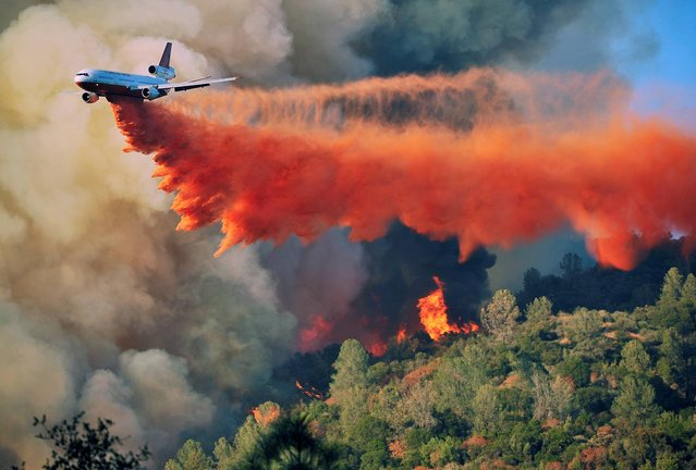An air tanker drops fire retardent on a fire which was burning on a ridge northeast of Oakhurst, Calif., Monday, August 18, 2014. One of several wildfires burning across California prompted the evacuation of hundreds of people in a central California foothill community near Yosemite National Park, authorities said. (Photo by Eric Paul Zamora/AP Photo/The Fresno Bee)