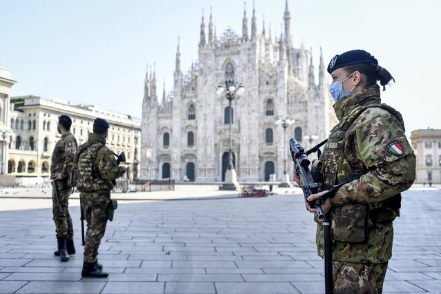 Soldiers patrol in front of the Duomo gothic cathedral in Milan, Italy, Sunday, April 5, 2020. The government is demanding Italians stay home and not take the leveling off of new coronavirus infections as a sign the emergency is over, following evidence that more and more Italians are relaxing restrictions the west's first and most extreme nationwide lockdown and production shutdown. (Photo by Claudio Furlan/LaPresse via AP Photo)