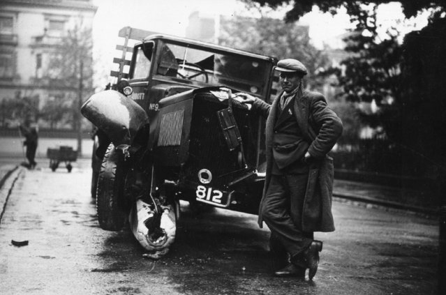 A driver leaning on his wrecked lorry, after he collided, and destroyed, a bollard in Holland Park, London, 25th May 1935. (Photo by J. A. Hampton)