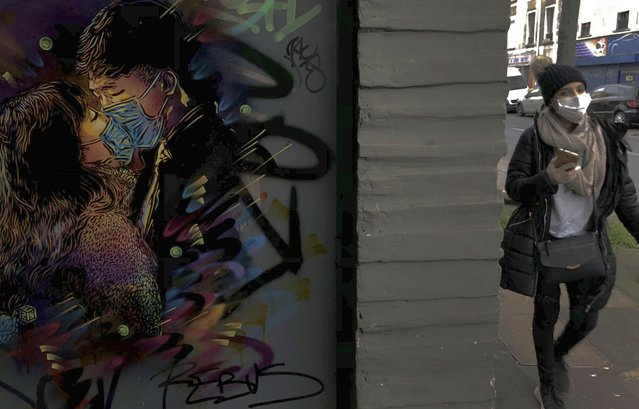A woman wearing a face mask walks past a painting by street artist C215 in Ivry-sur-Seine, outside Paris, Thursday, March 19, 2020. French President Emmanuel Macron said that for 15 days people will be allowed to leave the place they live only for necessary activities such as shopping for food, going to work or taking a walk. For most people, the new coronavirus causes only mild or moderate symptoms. For some it can cause more severe illness, especially in older adults and people with existing health problems. (Photo by Christophe Ena/AP Photo)