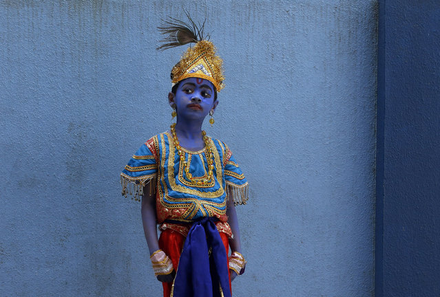A boy dressed like Hindu Lord Krishna waits to attend celebrations on the eve of Janmashtami at a school in Mumbai, India, Friday, September 4, 2015. The day marks the birth of Krishna. (Photo by Rajanish Kakade/AP Photo)