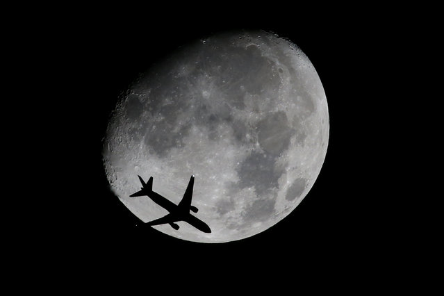 A passenger jet is silhouetted against the moon as it flies over Shanghai, China November 11, 2016. (Photo by Aly Song/Reuters)