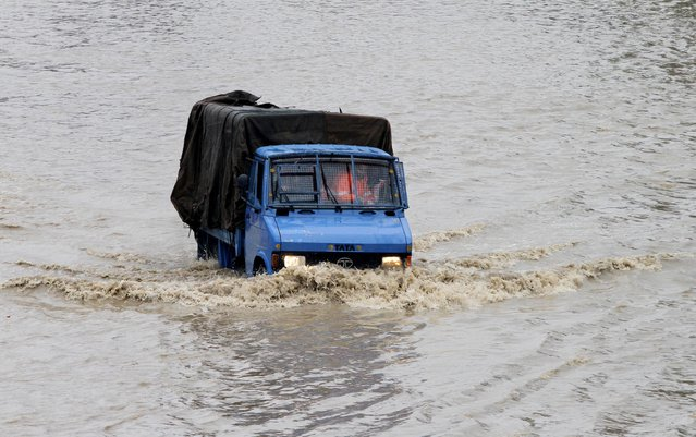 Rescue workers travel in a vehicle past floodwaters in Srinagar, India, Friday, September 5, 2014. (Photo by Mukhtar Khan/AP Photo)