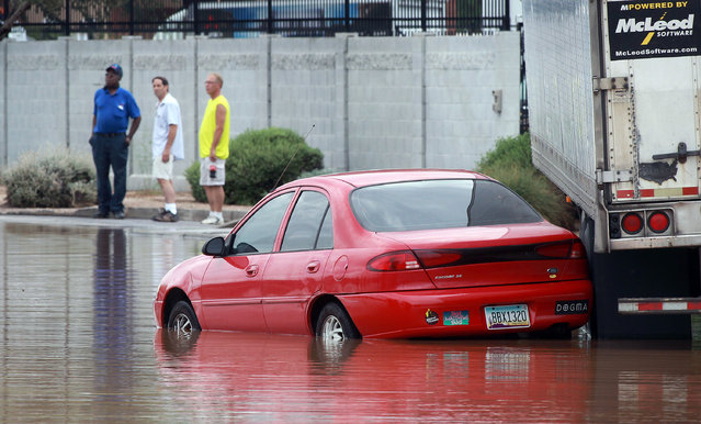 A vehicle sits stranded in about two feet of water on a flooded street near Roosevelt and 44th Avenue on Monday, September 8, 2014 in Phoenix. Monday's record breaking rainfall flooded several Phoenix-area freeways and local streets forcing closures with some areas reporting up to five inches of rain. (Photo by Ralph Freso/AP Photo)