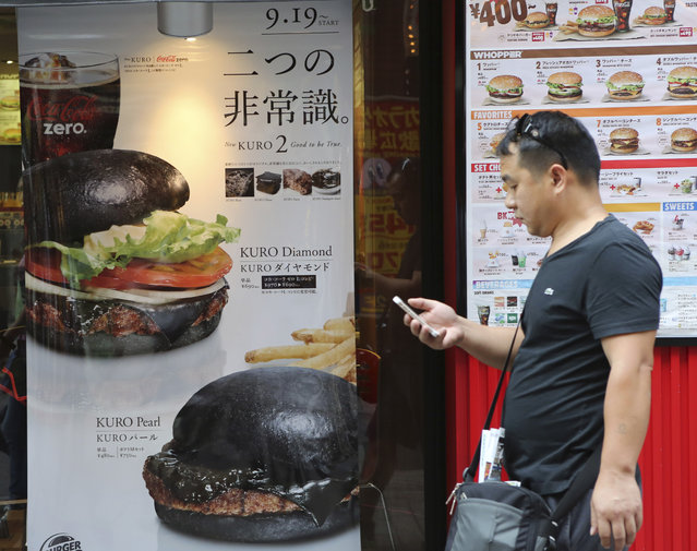 In this September 16, 2014 file photo, a man walks by a Burger King poster advertizing the Kuro Diamond burger, top, and the Kuro Pearl burger in front of its Shibuya restaurant in Tokyo. (Photo by Koji Sasahara/AP Photo)