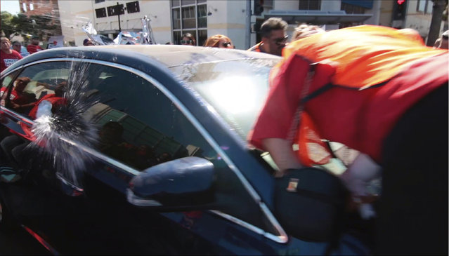In this still image taken from video and released by Unite Here Local 11, a motorist drives his car into marchers at an immigrant rights rally in Brea, Calif., Thursday, October 26, 2017. Brea police Chief Jack Conklin said none of the demonstrators sought first aid. He said he did not know why the man drove through the intersection where people were gathered. Police arrested 56-year-old driver Daniel Wenzek for investigation of assault with a deadly weapon, said Lt. Adam Hawley. (Photo by Antonio Mendoza/Unite Here Local 11 via AP Photo)
