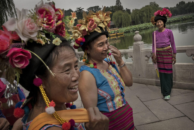 Chinese tourists from Yunnan Province wear tradtional clothing as they gather near Bei Hai Lake September 12, 2014 in Beijing, China. (Photo by Kevin Frayer/Getty Images)