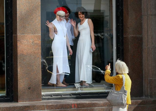 An elderly woman thumbs up to women posing in a shop window of a shopping mall in downtown Kiev, Ukraine, 19 September 2016. (Photo by Sergey Dolzhenko/EPA)