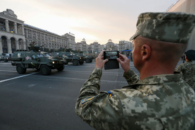 A Ukrainian serviceman takes a picture of armored vehicles during a rehearsal for the Independence Day military parade in central Kiev, Ukraine, August 19, 2016. (Photo by Valentyn Ogirenko/Reuters)