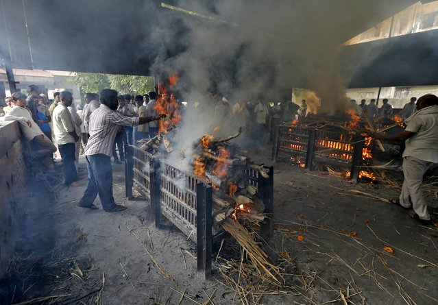 People stand around the pyres of Shantilal Boghra and his sister Bhanu Doberaiya, who died in a cooking gas cylinder blast in central Madhya Pradesh state on Saturday in Ahmedabad, India, September 13, 2015. (Photo by Amit Dave/Reuters)