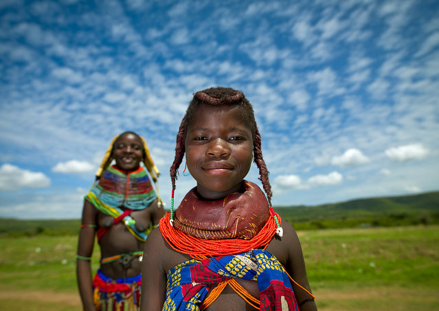 """""""Mumuhuila tribe girls – Angola. This little girl from the Mumuhuila tribe live near Chibia, in the south of Angola. She wears the traditional hairstyle and the big necklace. The necklace shows if she is teen or not. She is still a child as the necklace is red. On the hair, she wears the traditional hairstyle, made with a mix of trunk, oil and dried cow dung. Those girls live dressed like that, they were not dressed for me. In the back, her sister, who is already married, and so who wears the big beads necklace"""". (Eric Lafforgue)"""
