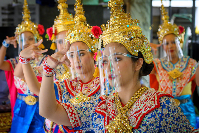 Traditional Thai dancers wearing protective face shields perform at the Erawan Shrine, which was reopened after the Thai government relaxed measures to combat the spread of the COVID-19 novel coronavirus, in Bangkok on May 4, 2020. Thailand began easing restrictions related to the COVID-19 novel coronavirus on May 3 by allowing various businesses to reopen, but warned that the stricter measures would be re-imposed should cases increase again. (Photo by Mladen Antonov/AFP Photo)