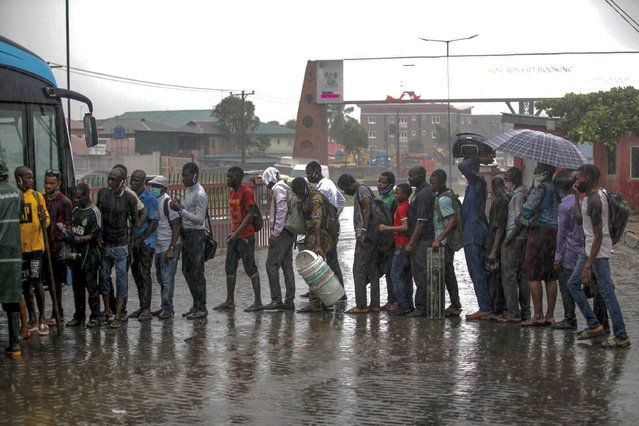 People queue in the rain to board a bus at a motor park in Lagos, Nigeria, 28 May 2020. The Lagos metropolitan government is considering the reopening of its economy over the next few weeks, following the partial lockdown to prevent the spread of the coronavirus disease. (Photo by Akintunde Akinleye/EPA/EFE/Rex Features/Shutterstock)