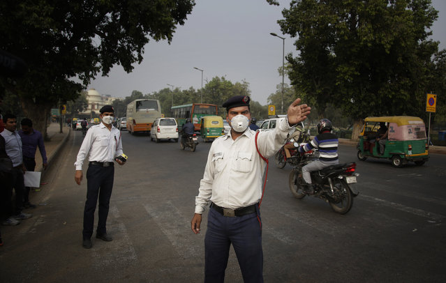 """In this November 16, 2017, photo, Ram Sharan, 28, right, a traffic police officer manages traffic in New Delhi, India. Sharan has spent the last three years working eight-hour shifts amid the capital's chaotic traffic. He said the Delhi police force has issued him and other officers with pollution masks.""""We face a lot of difficulties and problems. Our bodies get weak and we lose our immunity"""", he said. """"But duty is duty. I have to do it"""". Sharan said he feels like the public is not focusing on the problem. """"We live in nature but we don't support it"""", he said. """"Take cars. One house has four cars and all four people use different cars. Something should be done so they all leave in one car"""". (Photo by Altaf Qadri/AP Photo)"""