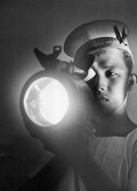 A Malay Seaman uses a blinker light to challenger approaching vessels around the minefields off the coast of Singapore, September 22, 1941. (Photo by AP Photo)