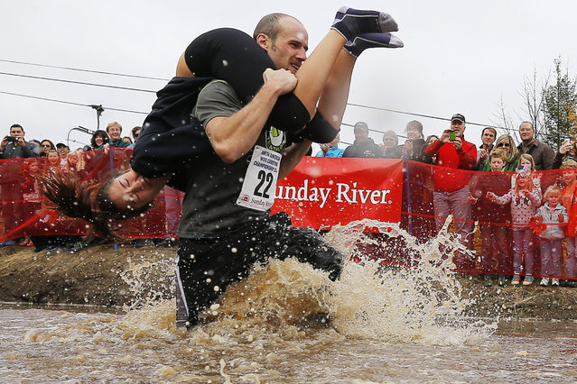 Richard Cannon carries Annie Leslie through the water pit while competing in the North American Wife Carrying Championship at Sunday River ski resort in Newry, Maine October 11, 2014. REUTERS/Brian Snyder
