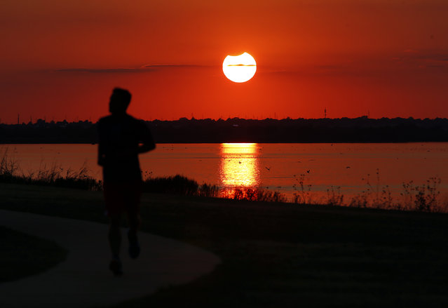 A jogger runs in front of the sun near the end of a partial solar eclipse at Lake Hefner in Oklahoma City, Thursday, October 23, 2014. (Photo by  Sarah Phipps/AP Photo/The Oklahoman)